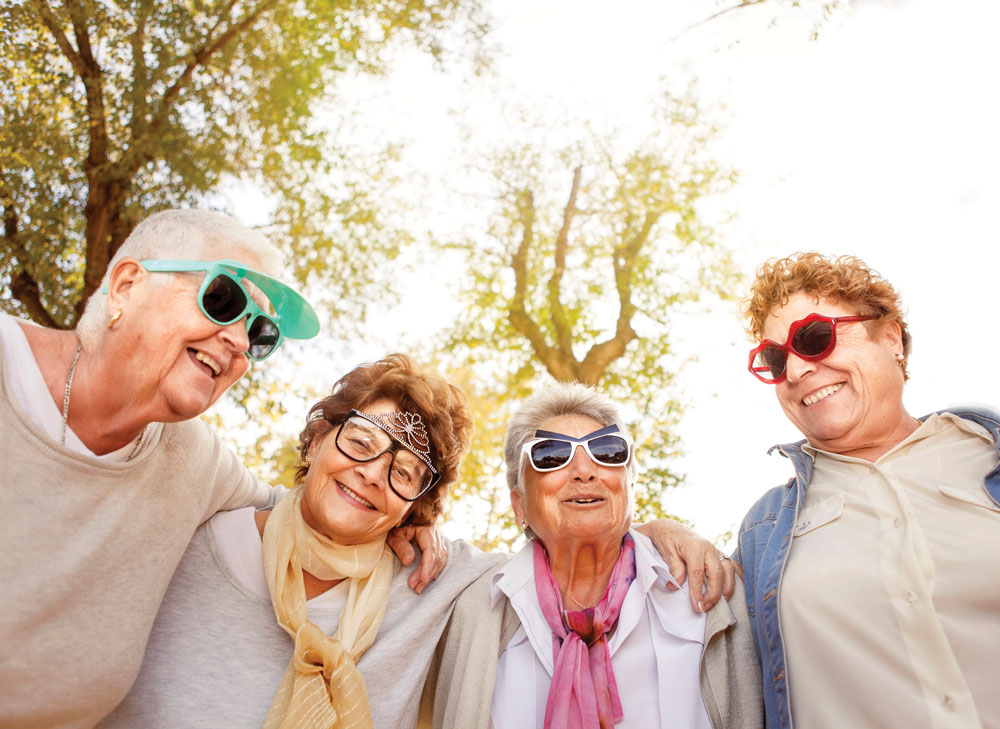 Group of older women wearing fun sunglasses pose with their arms around each other