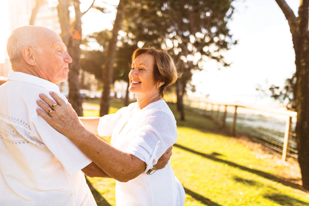 Charter Senior Living of Cleveland Residents couple dressed all in white smiles and dances together outdoors