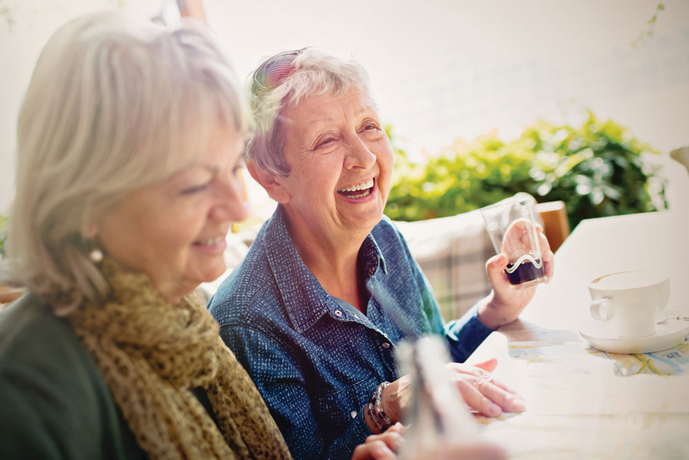 Two female residents of Charter Senior Living of Cleveland smile and share beverages while sitting at an outdoor table